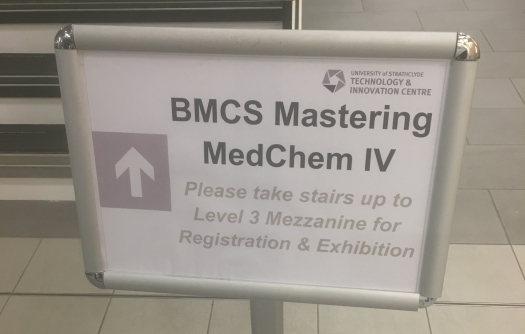 Picture caption: A metal sign at the bottom of some stairs pointing the way to the Mastering MedChem conference