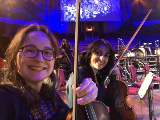 Picture caption: Fiona holding a violin sitting on the stage of the Royal Albert Hall with her orchestra desk partner Ouli.