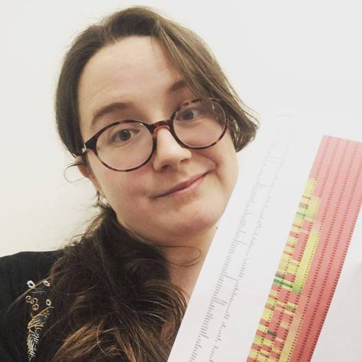 A selfie of me looking quite grumpy about some data I'm holding - a printout of a large table with lots of big numbers highlighted in red, orange and yellow