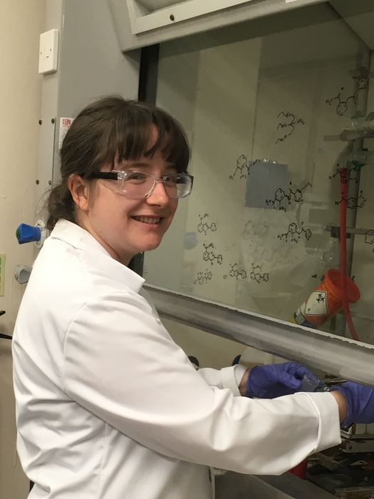 Fiona in lab goggles, white lab coat and purple gloves working in a lab fume cupboard